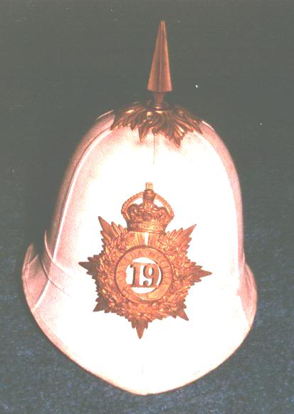 White pith helmet with large gold coloured badge on front with number 19 in the centre.