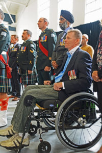 Captain Trevor Greene in wheelchair. This Seaforth officer was struck on the head by an axe in Afghanistan. Standing behind him wearing the turban is The Honourable Harjit Singh Sajjab, OMM, MSM, CD, Minister of National Defence.