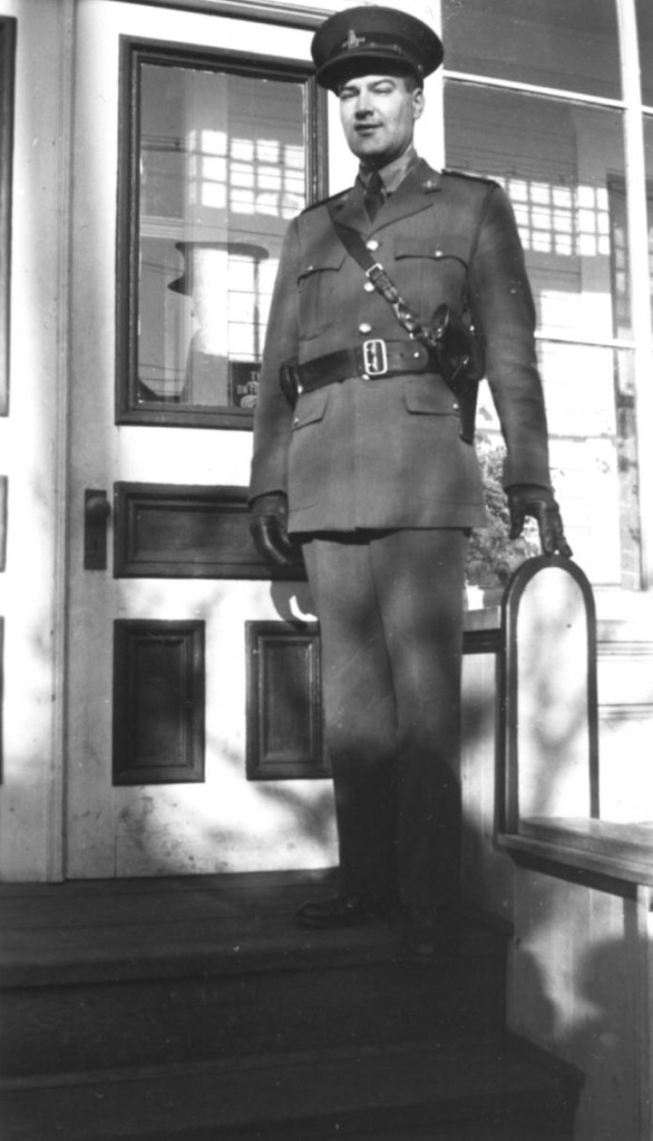 Police officer standing on front porch of a building. Constable Ted Brue, BC Provincial Police