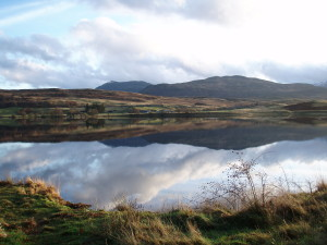 A Scotrtish lake with still water and hills behind. My MacGregors' ancestral home - Kinloch Rannoch in Perthshire, Scotland