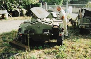 Man leaning on Ferret Scout Car and looking into it.