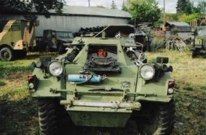 Man sitting in driver's seat of a Ferret Scout Car and looking out through the front hatch.