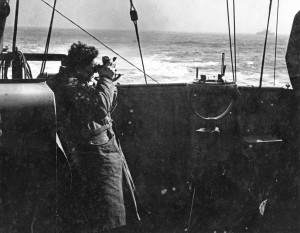 Naval officer in duffelcoat on bridge of ship using a sextant. Sub-Lieutenant Barry Brissendon from Victoria, B.C. taking a navigation sighting on board HMCS Malpeque 1942-43 (AHS p53 05 )