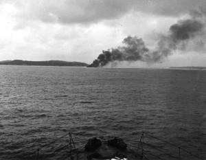 Smoke plume of burning sinking ship.