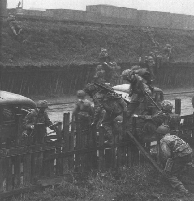 British Airborne troops training in England 1942-1944. Here they are crossing over a fence.