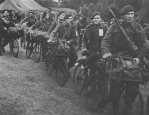 Royal Marine Commandos in Southern England immediately before D-Day, June 1944. They have BSA Airborne Bicycles with the Everest Carrier fitted to the front. They have finished their kit inspection, so the loaded rucksacks, rope, ammunition etc. are now loaded onto the bicycles as they head off to be loaded onto landing craft/ships.