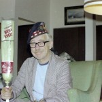 Man in housecoat and pajamas sitting holding a curling broom and wearing a curling hat. Dr. A H Pete Stevens at Christmas with a new curling broom
