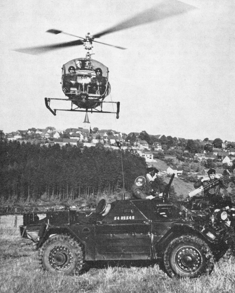 Canadian Army Ferret Scout Car 54-82542 shown in Germany with Canadian Army helicopter hovering overhead. Cdn Army Journal 1963 Vol XVII No2 p69
