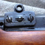 "No. 4 MK. I* (T) The front scope pad shows partly obliterated markings which are the Canadian Maltese Cross (meaning non-standard parts) and an upside down ""T"". The screws are double staked (to prevent screws coming loose) indicating heavy use."