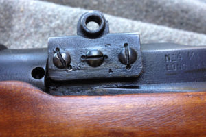"""No. 4 MK. I* (T) The front scope pad shows partly obliterated markings which are the Canadian Maltese Cross (meaning non-standard parts) and an upside down """"T"""". The screws are double staked (to prevent screws coming loose) indicating heavy use."""