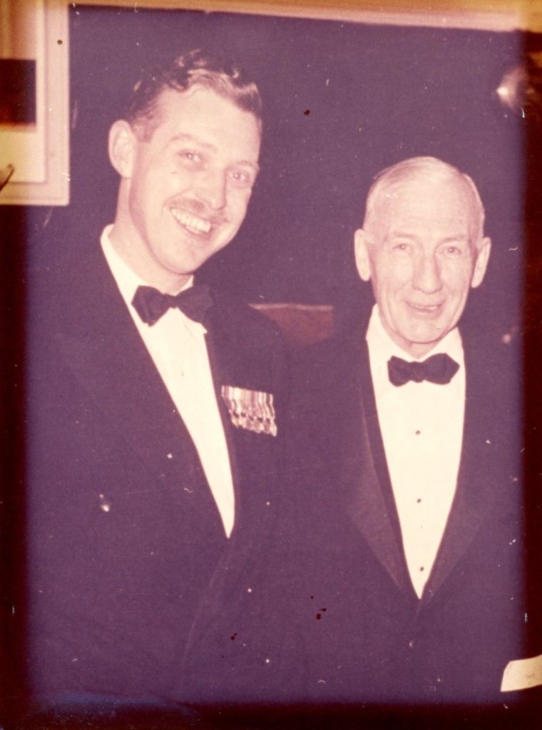 Photo of two men in black tie formal wear. Captain (?) A.H. Stevens with his father W.A.Stevens in the Officers' Mess at Lake Street Armoury in St. Catharines, Ontario. Late 1950s?