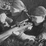 Observer with binoculars and sniper with rifle. 1944 Canadian snipers, Belgium.