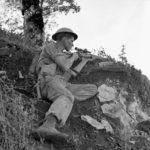 Sniper with helmet and No. 4 MK. I sniper rifle on a hiillside. 1943-10-06 Pte. J. E. (sic) McPhee, a sniper with the Seaforth Highlanders of Canada near Foiano, Italy. The only McPHEE was K74808 Pte. McPHEE, F. J. who served with the Seaforths 21 Aug. 1942 - 26 Dec. 1943. He was wounded 20 Jul. 1943 near Leonforte (West of Mt. Etna), Sicily and was Killed in Action 26 Dec. 1943 in or near Ortona, Italy. He was 23 years old and the husband of Mildred Ethel McPhee of Vancouver, British Columbia, Canada. He is buried in grave VIII. G. 2. Moro River Canadian War Cemetery. (L&AC MIKAN 3207117)