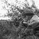 1944-10-09 Cpl. G. E. Mallery, a sniper covering other members of the Scout Platoon Queen's Own Cameron Highlanders of Canada, advancing towards Fort de Brasschaat, Belgium (L&AC MIKAN 3409540)