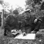 1944-10-09 Lieutenant W. C. Pearson on right briefing sniper Sgt. P. A. Rylaasden of the Scout Platoon, Queen's Own Cameron Highlanders of Canada at Fort de Brasschaet (L&AC MIKAN 3409536)