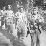 Five soldiers with rifles slubng over their shoulders, walking towards the camera. Lead man is a sniper with binoculars and cigarette. Sniper Canadians head for the Gothic Line in Italy (Hell & High Water)