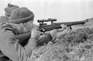 Sniper aiming his rifle. 1942-04-12 to 26. Canadian sniper in Assault landing course England P-14. Photo by Sgt. Al W. Grayston. (L&AC PA-213632 MIKAN 3599772)