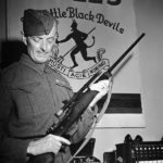 Soldier holding a sniper rifle in an office. 1942-07-30 An unidentified Corporal of the Royal Winnipeg Rifles holding a Ross sniper rifle with a Winchester A5 scope in Ottawa, Ontario. (L&AC PA-208603 MIKAN 3589887)