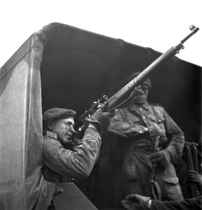 1943-04-23 Unidentified soldier sighting with his telescope equipped P-14 sniper rifle while sitting in the back of a 15 Cwt truck. 2 Canadian Infantry Division Sniper Training, England. Photo by Lieut. Grederick G. Whitcombe (L&AC PA-211643 MIKAN 3596210)