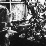 1944 British sniper Private Sutcliffe in Caen, France. Second view of him at the window.