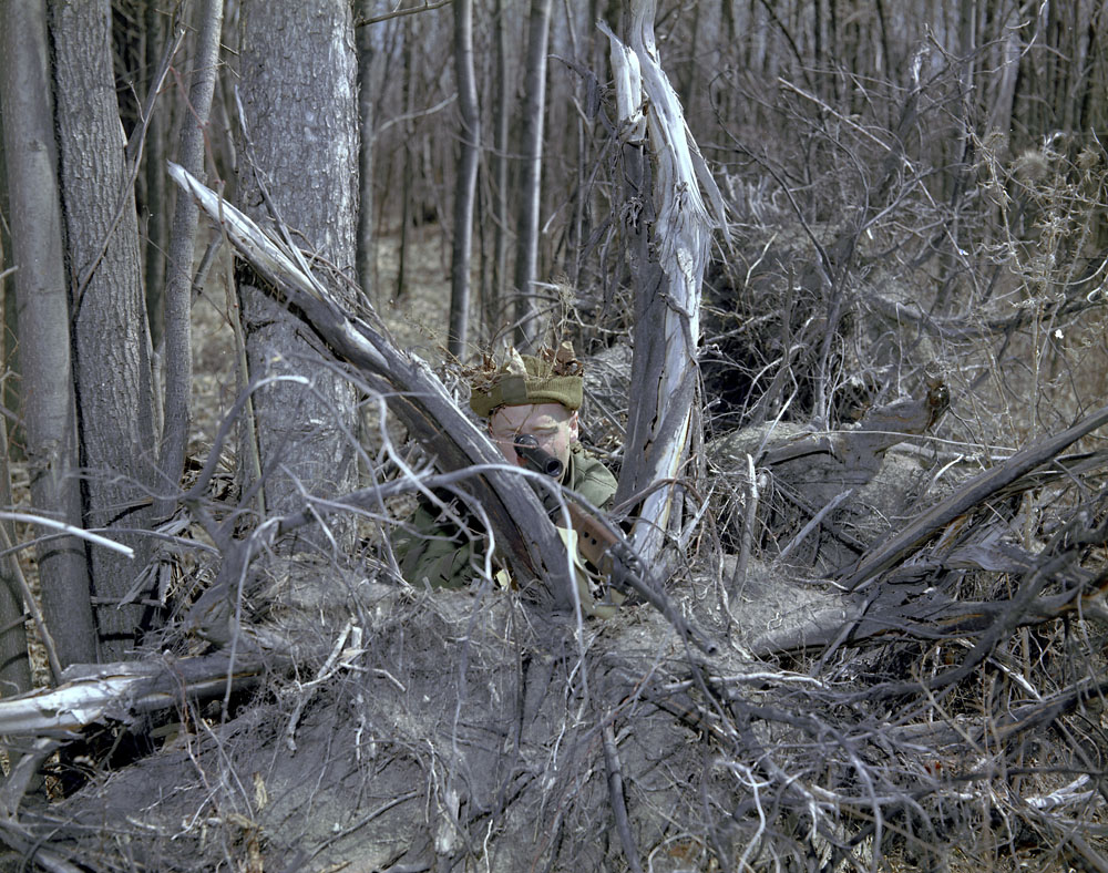 Front view of sniper hidden in brush. 1970 approx FNC1 or C1A1 with a Sniper Scope C1 during training at Camp Ipperwash Ontario (L&AC MIKAN 4235658)