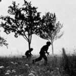 Two British WWII soldiers running among trees.