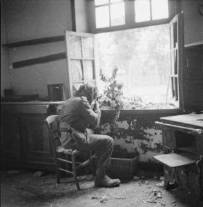 1944. British-sniper-Private Sutcliffe seated at a window in or near Caen, France. Caen is a major city just inland from the D-Day invasion beaches.