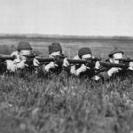 Five Canadioan snipers pose in prone shooting position.