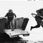 Brtiish soldier leaping off of a landing craft carrying his rifle.