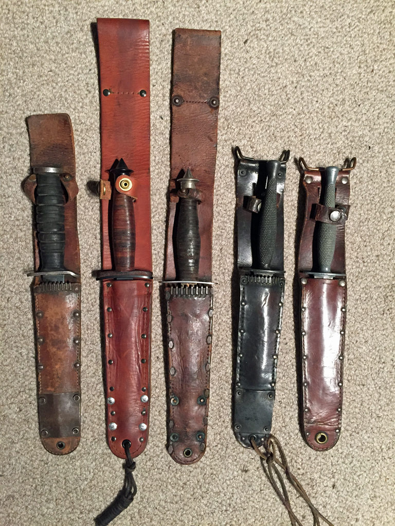 "Knives in their scabbards. Left to right: U.S. M3 Trench knife is an ""unfinished (but used) M6 scabbard.; Case V-42 reissue post-war; WWII issue Case V-42 of Sgt. Jack W. Stallings 1-1 FSSF; 1 Canadian Parachute Battalion ""Killing Knife""; USMC Stiletto."