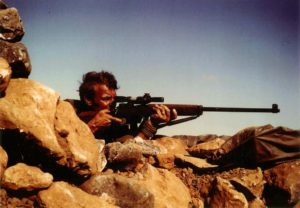 Sniper aiming his rifle. British Special Air Service (SAS) sniper in Oman in the 1970s with an L42A1 7.62mm sniper rifle. The cloth (groundsheet?) under the muzzle was likely to present the muzzle blast from stirring up a dust cloud which would reveal the sniper's position.