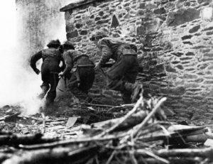 Three Brtiish soldiers rusging a stone building.