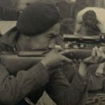 Canadian solider aiming with a Lee-Enfield sniper rifle.
