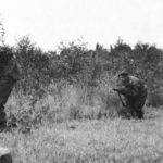 Four Canadian snipers creeping along the edge of some bushes in Belgium in 19044.