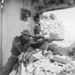 Sniper aiming his rifle from a damaged building.