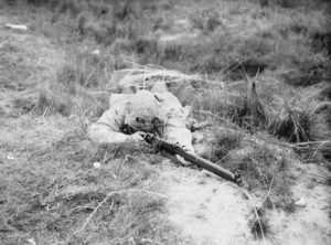 Sniper camougflaged and prone with rifle.