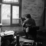 British sniper aiming out of a window.