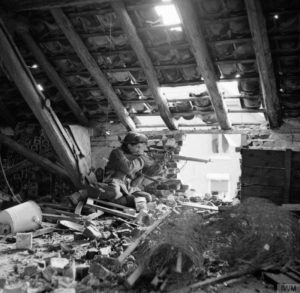 """Sniper in attic British. """"C"""" Company 5 Battalion, Black Watch 51 Highland Division, Gennep Netherlands . Posed photo as position is unsafe. By 5 AF&PU © IWM (B 14628)"""