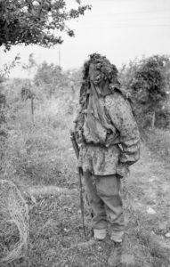 Sniper school camouflage demonstration. Man appears to be wearing a German camouflage jacket, so it may be instruction on recognizing the enemy sniper. Normandy 27 JUL 44 © IWM (B 8177)