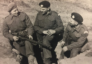 Three men talking with their feet in a trench with a sniper rifle.