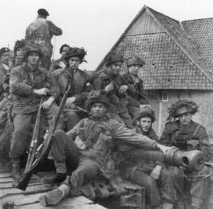 Canadian paratroopers riding on a British armoured vehicle.