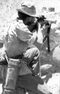 British sniper in Aden in 1964 aiming his No. 4 MK. I (T). He has a Case No. 8 MK. 2 slung to hold the No. 32 MK. 3 scope and its mounting bracket when they are not on the rifle. M1907 leather sling on the rifle. He has an unusual cartridge belt and he also has a clasp knife hanging down on the right side from a lanyard. (TMSS1914 p45)