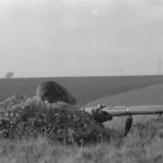 Canadian sniper in training England circa 1940-1941 behind rock. He is using a No. 1 MK. III* rifle without scope. (L&AC MIKAN 3607512)