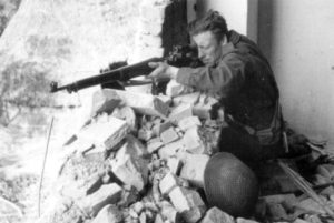 Canadian sniper with his No. 3 MK. I (T) with a Model 1913 Warner & Swasey scope at Ortona, Italy. These scopes were originally mounted on the Ross rifle, but some were fitted to No. 3 MK. I (Pattern 1914) rifles. (L&AC PA130609)