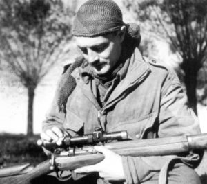 Sergeant H. A. Marshall cleaning his No. 4 MK. I (T) sniper rifle's No. 32 scope.