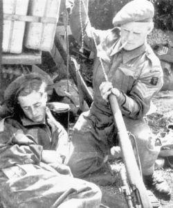 Sniper believed to be of the 5th Battalion, The East Yorkshire Regiment of the 50th (Northumbrian) Division cleaning his No. 4 MK. I (T) rifle using a German pull-through while another man sleeps. This Battalion was [part of the 69th Infantry Brigade which was pulled back to the UK in December 1944 so this photo is likely between June 6 1944 and December 1944. (Royal Armouries Library)