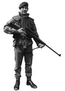 British Royal marine (?) standing holding a sniper rifle.
