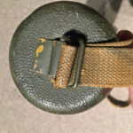 Bottom end of carrying case showing the buckle for attaching the carrying strap.