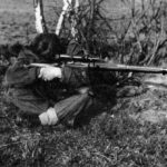 A seated British sniper, legs crossed, resting his elbows on his knees while aiming his sniper rifle.