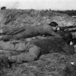 """WWII British """"sniper pair in training. """"One shooting, one observing with telescope ... around cover. Notice the tremendous difference the sniper smock and camouflage veil man in a man's 'merging into the ground' compared with the battledressed and bareheaded observer. WBSTTR - Shore 1948 fp 263"""